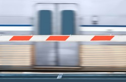 Red and white striped train crossing barrier and speeding urban commuter train. Focus on barricade. Train doors and motion blur background.