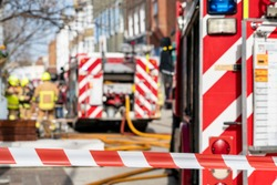 Red and white striped warning tape prevents people entering an incident in a town centre. In the distance, and intentionally out of focus, fire fighters in uniform, fire appliances and yellow hoses.