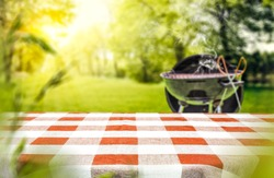 Red and white tableclothe in garden of free space for your decoration. Grill with smoke on grass.