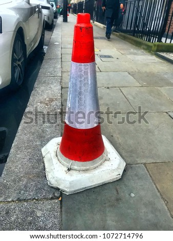 Red and white traffic cone on pavement, parked luxury car, pedestrian on London street #1072714796