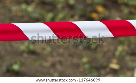 Red and white warning tape stretched across a blurred background