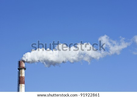 Red and white weathered chimney with smokestack against a blue sky