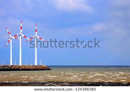 Red and white windmills towers over a landscape of sea
