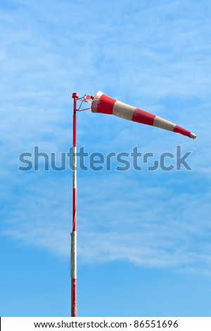 Red and white windsock against a bright blue sky