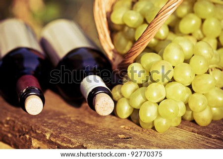 Red and white wine bottles and bunch of grapes in basket on wooden table. Retro toned image
