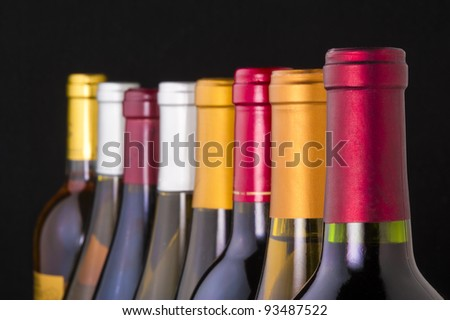 Red and white wine bottles in a row with limited depth of field