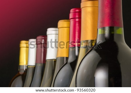 Red and white wine bottles lined up in a row