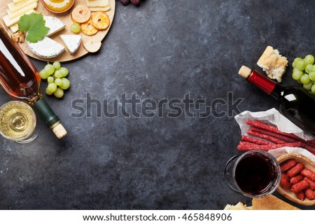 Red and white wine, grape, honey, cheese and sausages over stone table. Top view with copy space
