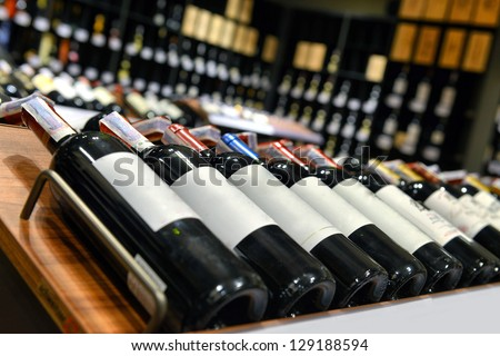 Red and white wine in bottles in wine shop #129188594