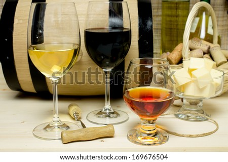 Red and white wine in glasses, brandy. On the background of a barrel and wine corks basket, bowl with cheese and a bottle of wine, a corkscrew.