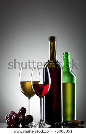 Red and white wine in glasses with grape and bottles - stock photo