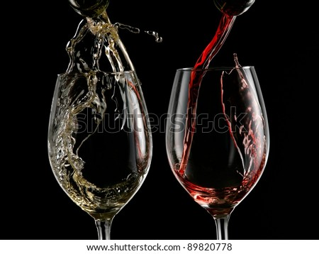 Red and white wine start pouring into two wineglasses on black background