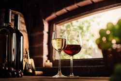 Red and white wine tasting in the winery: full wine glasses next to a window and lush vineyard on the background, winemaking concept