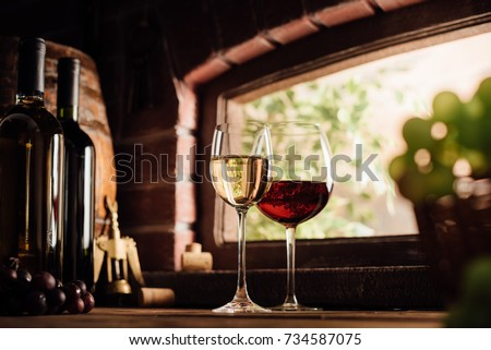 Red and white wine tasting in the winery: full wine glasses next to a window and lush vineyard on the background, winemaking concept - Shutterstock ID 734587075