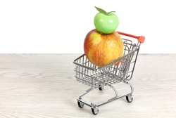 Red and yellow apple and ceramic green apple inside a miniature shopping cart on a white wooden table over a white background