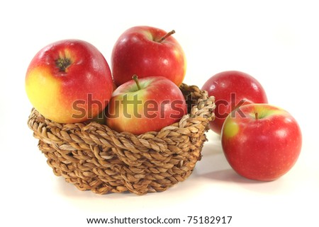 red and yellow apples in the basket before a white background
