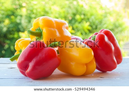 Red and yellow bell peppers outdoors
