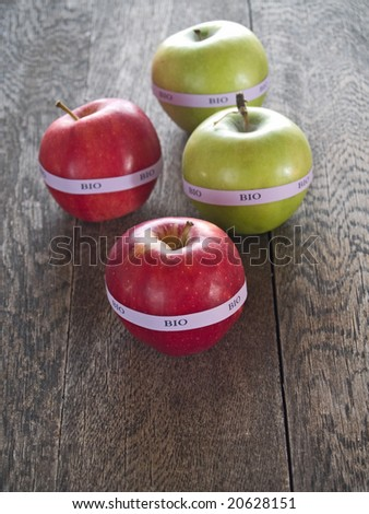 Red and yellow bio apples on a rustic wooden table