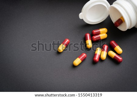 red and yellow capsules pill spilled out from white plastic bottle container. Global healthcare concept. Antibiotics drug resistance. Antimicrobial capsule pills. Pharmaceutical industry. Pharmacy.