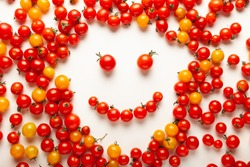 Red and yellow cherry tomatoes, fresh bright organic vegetables. Smiling face.