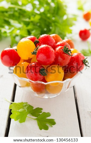 Red and yellow cherry tomatoes in glass bowl
