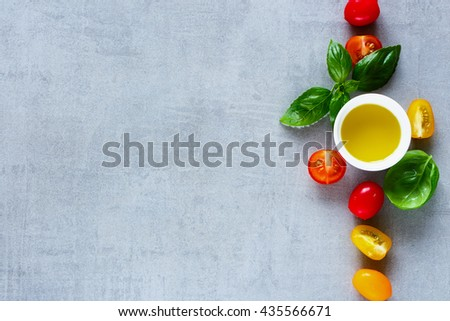 Red and yellow cherry tomatoes, olive oil with fresh basil leaves on light grey table, top view. Simple Italian food concept background with space for text.