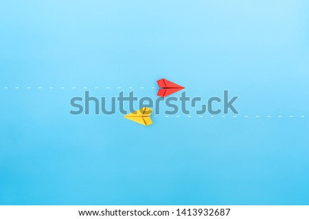 Red and yellow paper planes flying in different directions, blue background. dissenting opinion, divergent views concepts