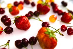 Red and yellow ripe cherries and strawberries. Berries are randomly scattered on a white background. Summer background of juicy fruits.