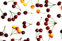 Red and yellow ripe cherries. The berries are scattered randomly on a white background. Summer background of juicy fruits.