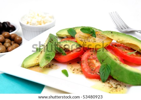 Red and yellow sliced tomatoes with  avocado, fresh oregano leaves with an olive oil and raspberry vinaigrette dressing on a square white plate with green and black olives in small bowls