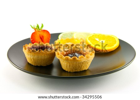 Red and yellow small jam tarts with slices of lemon, lime, orange and strawberry on a black plate on a white background
