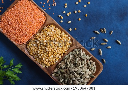 Red and yellow split lentils or Chana Dall with Cardamom on wooden platter on a blue background with copy space available on right Photo stock ©