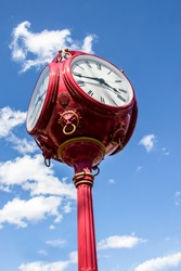Red antique four sided street standing clock against blue sky with fluffy clouds - vertical