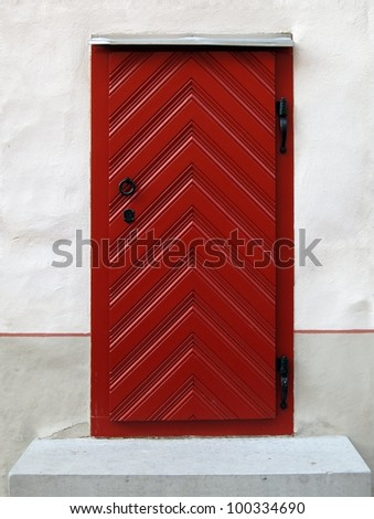 Red antique wooden door with metal handle and white plaster wall around