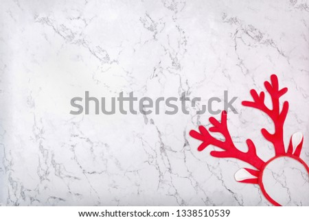 Red antlers of a deer headband on marble background. Pair of toy reindeer horns on white marble texture #1338510539
