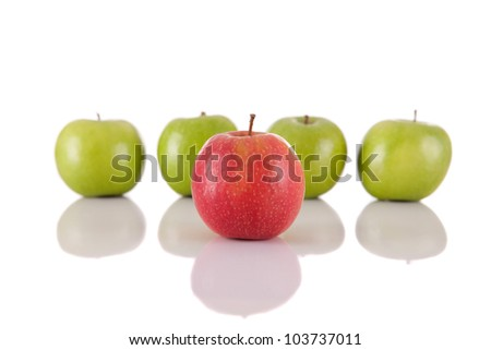Red apple among green apples isolated on a white background