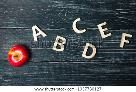 Red apple and alphabet made of wooden letters on a dark background of a school board. Apple for the teacher. The concept of an elementary school, college, university, education. Education, education,  #1037730127