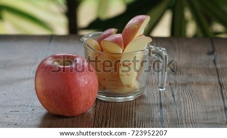 Red apple and apple slide in pieces put in a measure glass cup.  #723952207