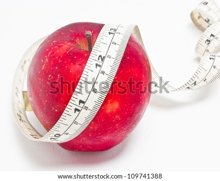 Red apple and measure tape isolated on white background.