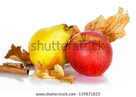 red apple and pear with oak leaves and cinnamon on a white background