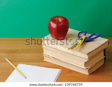 Red apple and scissors on pile of books