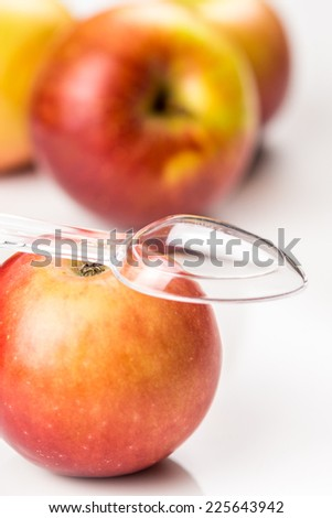 red apple and translucent medicine spoon on the table symbolizing that drinking and eating of apple products prevents diseases and is full of vitamins, other apples at background