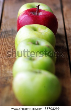 red apple between green apples on wooden surface