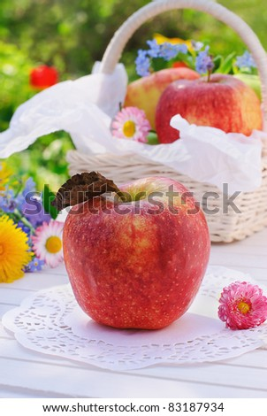 Red apple, flowers and basket on white garden table
