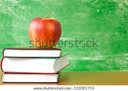 red apple on a pile of books against dirty chalkboard