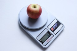 Red apple on digital weights scale isolated on white background closeup.