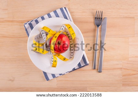 Red apple on plate with measure tape, knife and fork. Diet food on wooden table.  Above view
