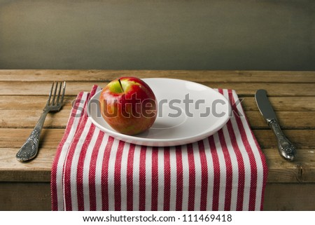 Red apple on white plate, table arrangement.