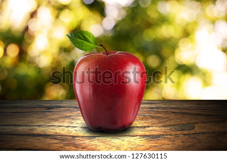 Red Apple on wood with summer scene background