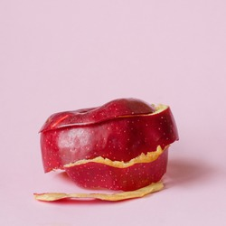 Red apple peel on pink background as a symbol of recycling circulate economy
